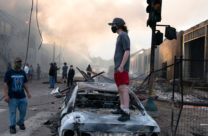 A man stands on a burned out car on Thursday morning as fires burn behind him in the Lake St area of Minneapolis, Minnesota. Photo: Lorie Shaull from St Paul, United States
