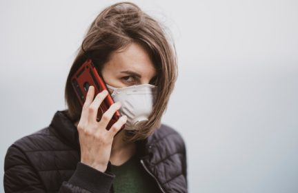 A woman wearing a valved respirator and talking on a cell phone
