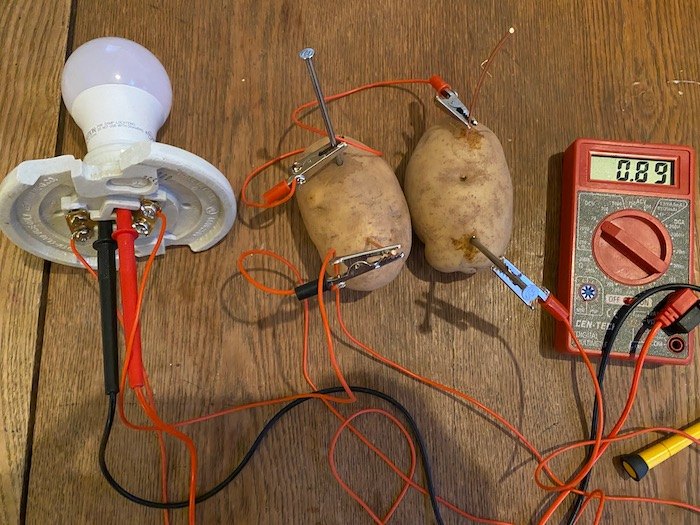 Two potatoes hooked up to a light bulb