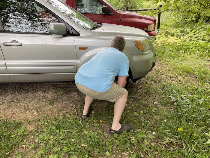Squatting behind a vehicle's engine block and front passenger wheel