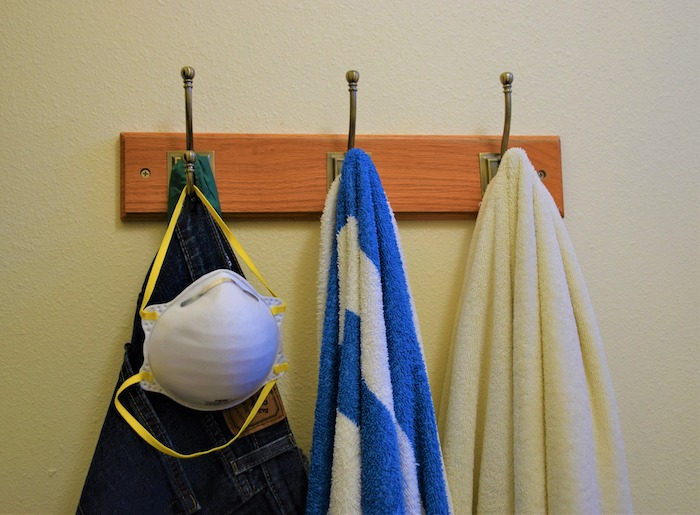N95 mask on a hook along with jeans and towels