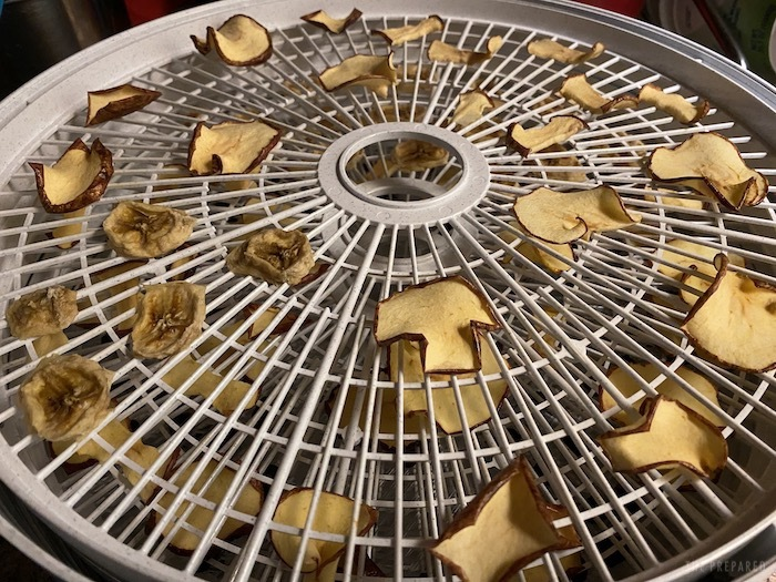 Brown, curled pear chips on a white dehydrator rack.